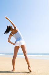 Sportliche junge Frau dehnt sich am Strand