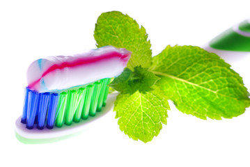 Toothbrush, toothpaste and fresh leaves of mint on a white backg