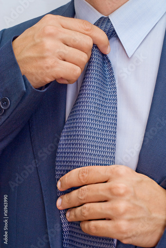 Businessman corrects tie
