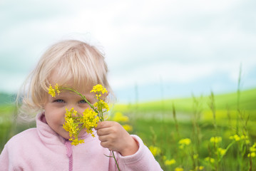 Little girl smelling flower in field