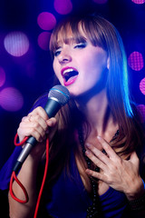 Portrait young Woman Singing into Microphone