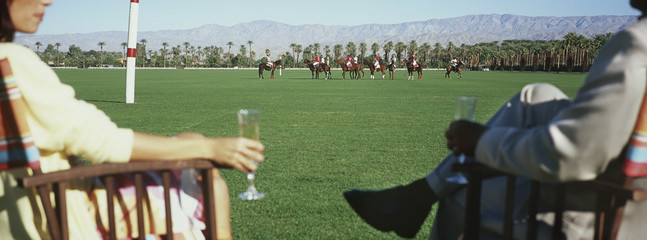 Couple drinking champagne, sitting watching polo