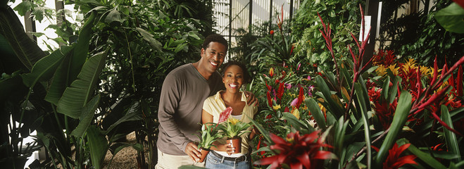 Couple holding plants at garden center, portrait