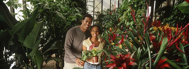 Couple holding plants at garden center, portrait