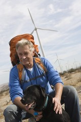 Senior man with backpack near wind farm