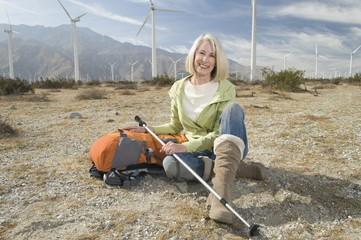 Senior woman with backpack near wind farm