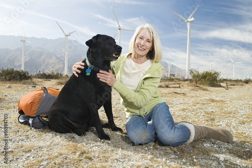 Senior woman with dog near wind farm