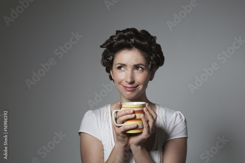 Coy young woman with hair curlers holding cup