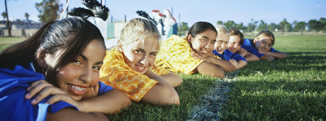 Teenage girls 13-16 lying in row on soccer field
