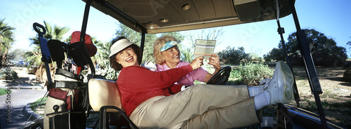 Two senior women laughing in golf cart