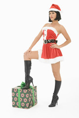 Mrs Claus standing with one foot on gift