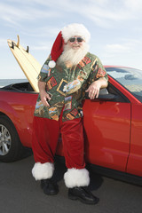 Father Christmas stands by red convertible with surfboard
