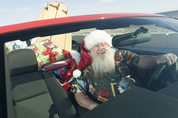 Father Christmas sits in red convertible with surfboard