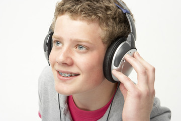 Portrait of Smiling Teenage Boy Listening to Music