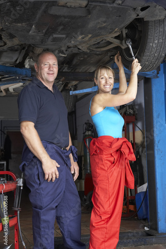Male and female mechanics working on car