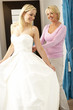 Bride trying on wedding dress with sales assistant