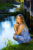 Beautiful young woman sitting on the shore of a stream.