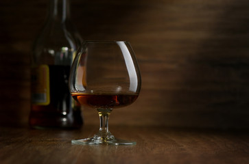 Cognac in the big glass on a dark background