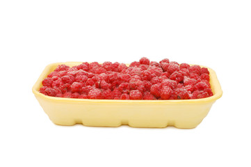 Plastic tray with the frozen raspberry