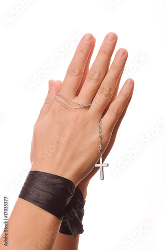 Woman is praying holding her cross. On white background.