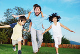 Happy family running outdoor, on beautiful garden