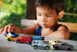 Children playing with cars toys outdoor in summer time