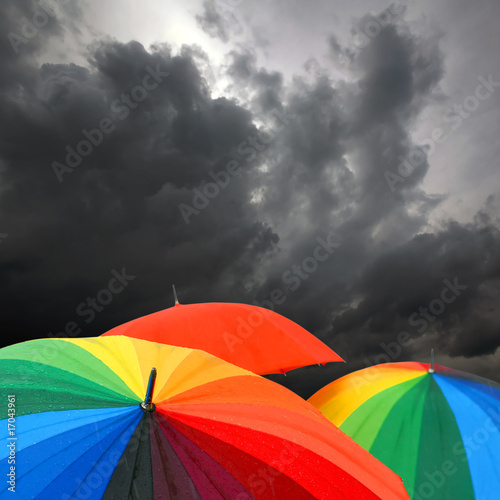 rainbow colored umbrella's in rainy autumn weather