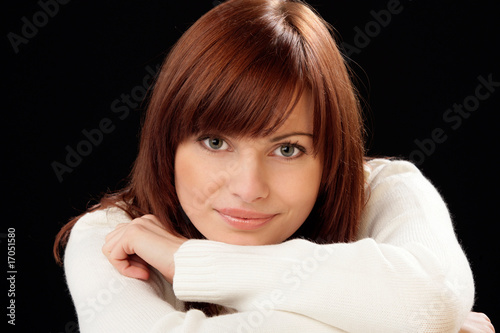 Woman on black background resting her head on hands