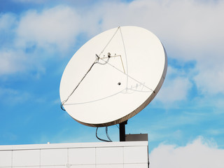 Satellite dish on the modern building roof corner
