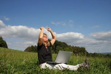 Frau mit Laptop auf grüner Wiese in Siegerpose
