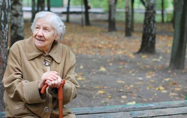 elder woman using her cane to walk