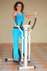 smiling young woman on training apparatus, full body