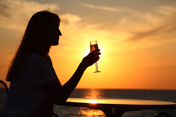 Female silhouette on sunset at  table with  glass in hand