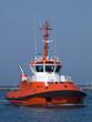 A huge orange tugboat in a harbor