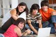 Jeunes garçons et filles assis devant un ordinateur portable