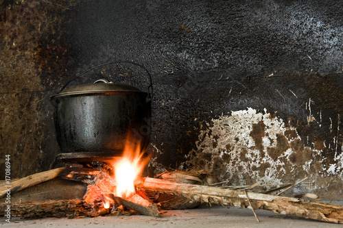 A soot blackened iron pot over an open fire in a rural kitchen