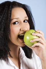 Young woman bite an green apple