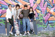 Jeunes garçons et filles devant un mur de graffitis