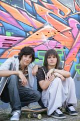 Adolescents assis devant un mur de graffitis