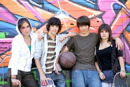 Adolescents devant un mur de graffitis