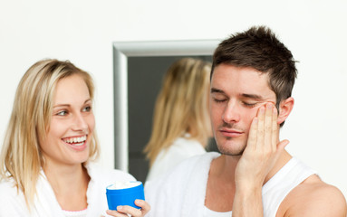 Man putting cream on his face with her wife