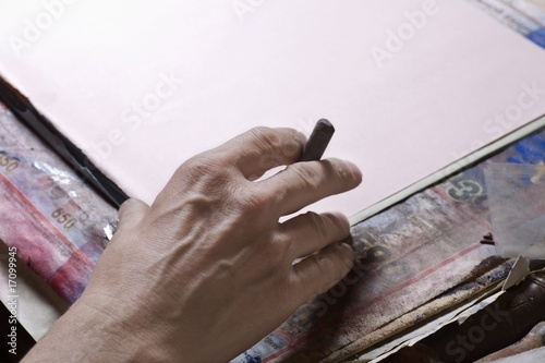 Man holds pastel preparing to draw