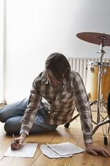 Young man sits on floor near drum kit writing music