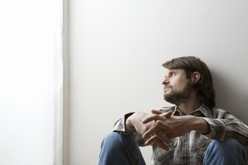 Young man in checked shirt sits with hands clasped against a wall