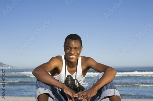 Man sitting on beach with with football boots round his neck