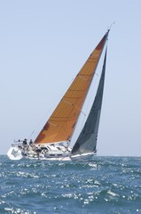 Yacht with yellow sail competes in team sailing event, California