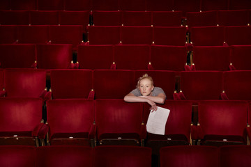 Young woman sitting in theatre stalls