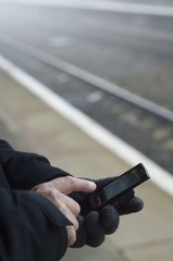 Man stands on train platform texting from mobile phone