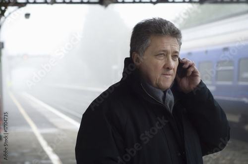 Man stands on train platform with mobile phone