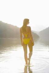 Woman in yellow bikini stands at edge of lake
